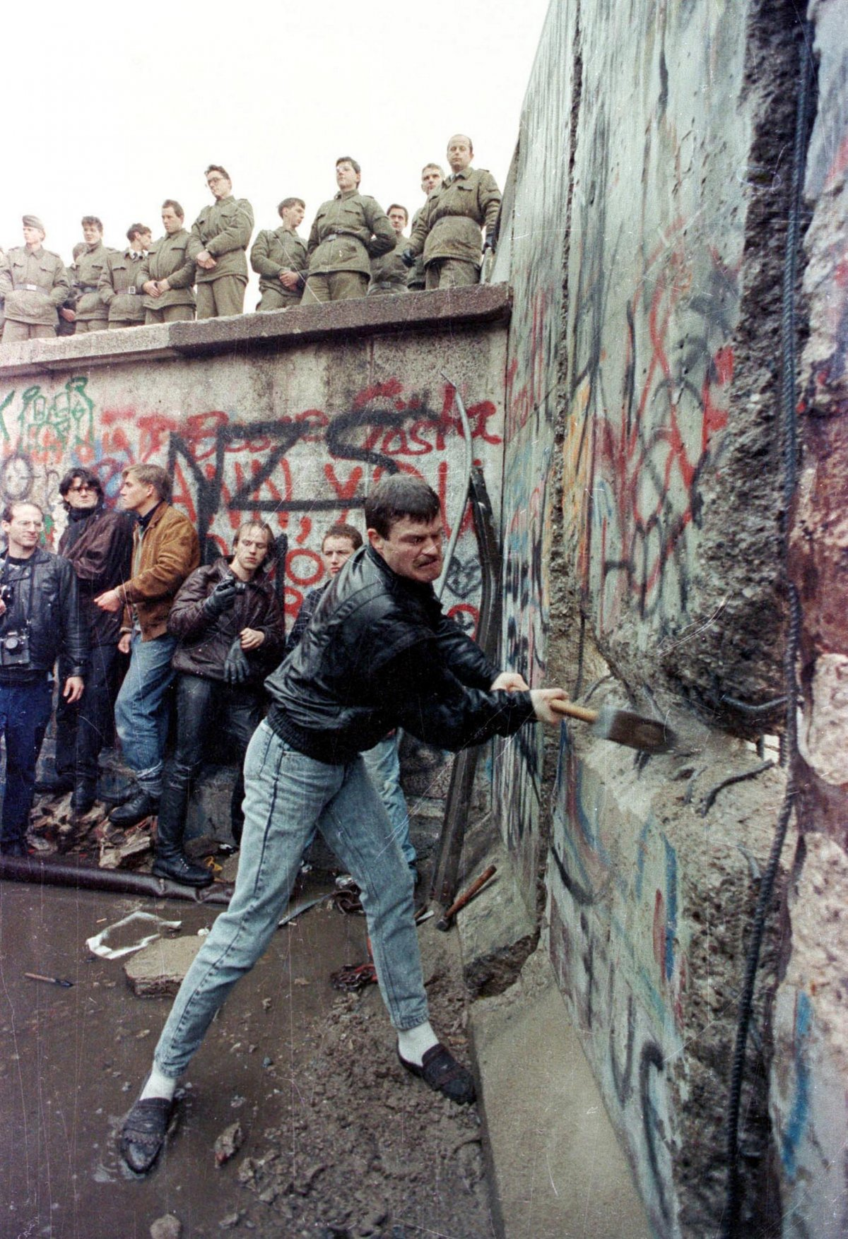 a-demonstrator-pounds-away-at-the-berlin-wall-as-east-berlin-border-guards-look-on-from-above-the-brandenburg-gate-in-berlin-in-november-1989
