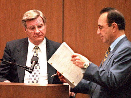 LOS ANGELES, CA - MARCH 21: O.J. Simpson Defense attorney Robert Shapiro(R) shows Los Angeles Police Detective Philip Vannatter(L) some of his previous testimony in the Simpson's murder case 21 March during cross-examination. Vannatter is one of the lead detectives in the case. AFP PHOTO (Photo credit should read POO/AFP/Getty Images)