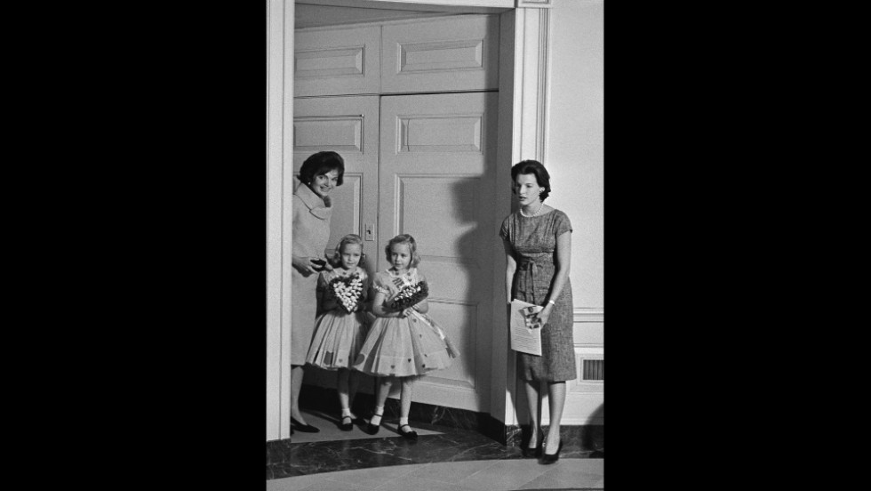 "Jacqueline Kennedy escorts the ""Heart Fund Twins,"" Donna, left, and Debbie Horst into the White House Diplomatic Reception Room during an opening ceremony for the American Heart Association's fund-raising drive in Washington on Feb. 1, 1961. At right is Pamela Turnure, press secretary to the first lady. (AP Photo/Bill Allen)"