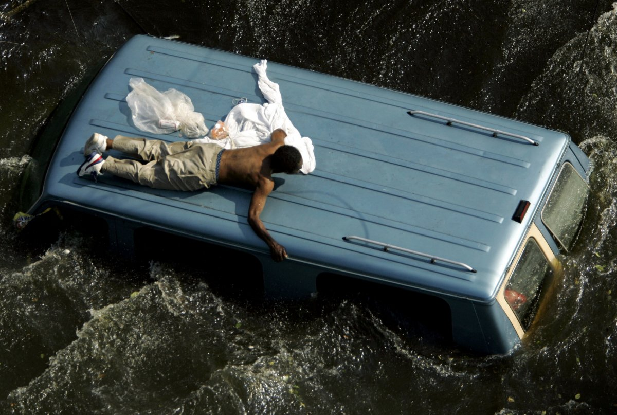 a-man-clings-to-the-top-of-a-vehicle-before-being-rescued-by-the-us-coast-guard-from-the-flooded-streets-of-new-orleans-in-the-aftermath-of-hurricane-katrina-2005