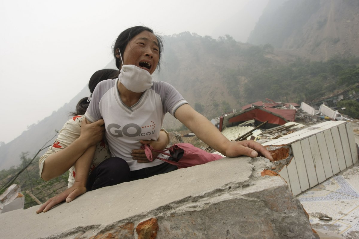 a-woman-cries-as-she-cannot-find-her-husband-and-4-year-old-daughter-on-the-top-of-the-ruins-of-a-destroyed-school-in-earthquake-hit-sichuan-province-of-china-on-may-17-2008