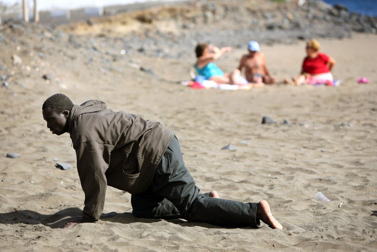 a-would-be-immigrant-crawls-on-the-beach-after-his-arrival-on-a-makeshift-boat-on-the-gran-tarajal-beach-in-spains-canary-island-of-fuerteventura-on-may-5-2006