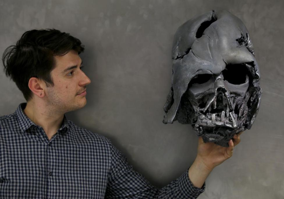 "A worker holds a replica of Darth Vader's melted helmet from ""Star Wars: The Force Awakens"", in the Propshop headquarters at Pinewood Studios near London, Britain May 25, 2016. REUTERS/Peter Nicholls"
