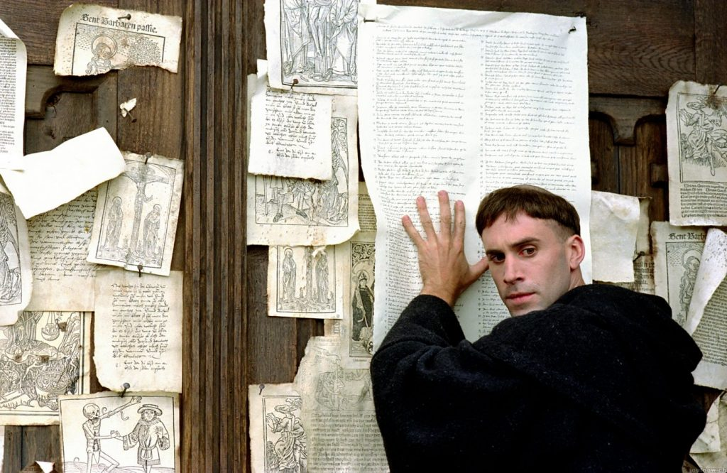 "Joseph Fiennes portraying Martin Luther, in the film ""Luther"", nailing his 95 thesis to the door of Wittenberg's church. [PHOTO: Read the Spirit]"